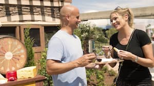 A man and a woman smile and sample wine and cheese at Epcot