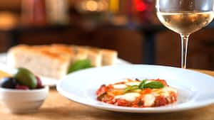 Italian cuisine prepared with marinara sauce and mozzarella, and plated beside a glass of wine