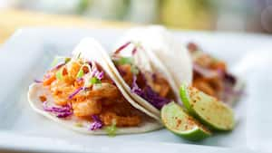 Limes sprinkled with chile-lime salt accompany a trio of tacos filled with crispy shrimp and cabbage