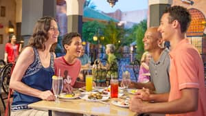 At an outdoor table surrounded by other diners and palm trees, a couple and their 2 teenage sons laugh and chat while enjoying drinks and delicious looking food in a Moroccan-style setting