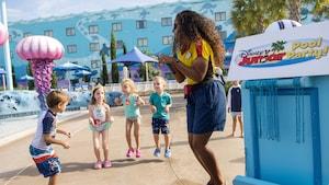 Un grupo de Visitantes en trajes de baño rodean a un Miembro del Elenco en una fiesta en la piscina de Disney Junior