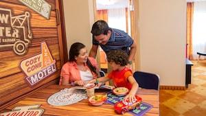 Mãe, pai e seu filho pequeno apreciam o café da manhã juntos no Disney's Art of Animation Resort