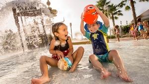 Une jeune fille et son petit frère font des éclaboussures dans une aire de jeux aquatiques d'un hôtel Disney