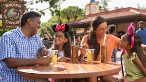 Uma família ri em uma mesa, perto da sinalização onde se lê Tortuga Tavern
