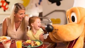 Mãe e filha riem juntas, sentadas a uma mesa perto do Pluto, da Disney