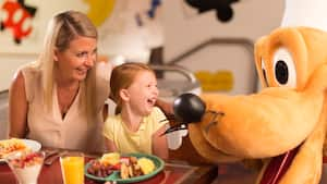 A laughing mother and daughter sit at a table next to Disney's Pluto