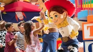 Um grupo de crianças sorridentes cumprimenta Woody e Jessie