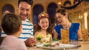 Una niña con una corona, sentada en una mesa de un comedor grande, con su madre, su padre y su hermano