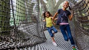 Dos visitantes se ríen mientras caminan a través de un área de juegos con sogas en Club Disney
