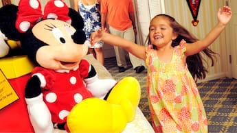 A small girl in a hotel guest room with her parents is overjoyed to find a large Minnie Mouse plush on the bed