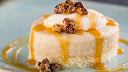A round cheesecake dripping with a syrupy sauce and topped with nuts