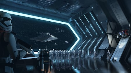 A dagger shaped Imperial Star Destroyer moves toward a docking bay staffed by Stormtroopers at attention