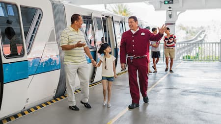 Huéspedes salen del monorriel guiados por un Miembro del Elenco de Disney