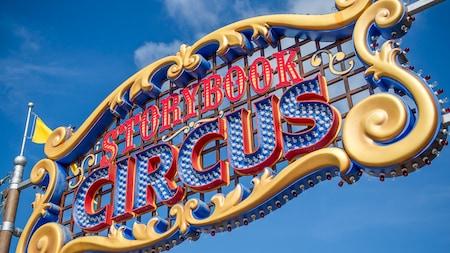 """Un letrero ornamental grande con el texto """"Storybook Circus"""" en letras iluminadas"""