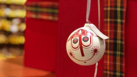 Um enfeite de Natal, decorado com o estilo moderno da artista Disney Mary Blair, pendurado em uma fita