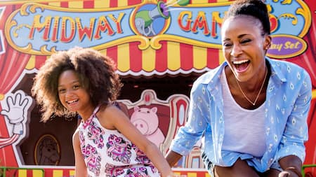 A mother and daughter enjoy the attractions at Toy Story Mania