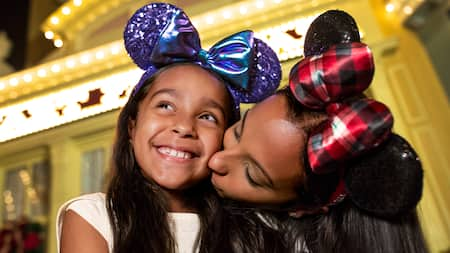 A mother and daughter wearing Minnie Mouse headgear share a happy moment at Walt Disney World Resort