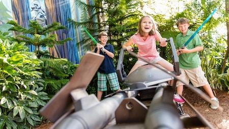 Niños con sables luminosos en medio de utilería inspirada en StarWars, en Star Tours:  The Adventures Continue