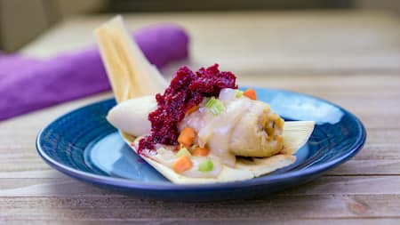 A plate of the turkey stuffed tamale topped with celery, carrots and cranberry sauce