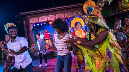 Una pareja baila cerca de actores vestidos con atuendos exóticos