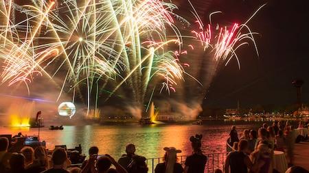 Fuegos artificiales en el cielo, sobre un lago y una multitud de gente mirando