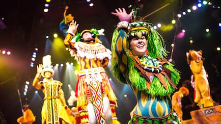 Performers dressed in exotic attire wave on a stage