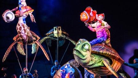 Actores sostienen muñecos de los Personajes de la película Finding Nemo de Disney•Pixar
