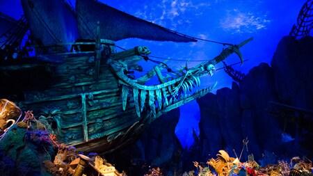 Un barco pirata bajo el agua rodeado de tesoros, barcos naufragados y corales
