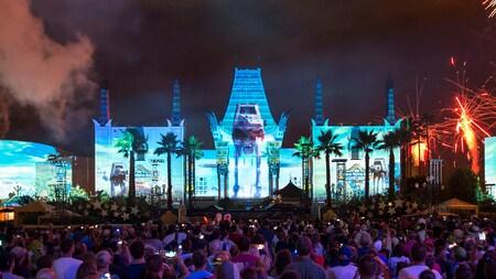 Una imagen de un AT-AT es proyectada en un teatro cerca de fuegos artificiales ante una multitud que observa