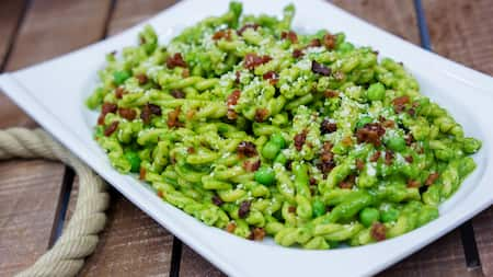 A rectangular plate of spiral twist pesto pasta is covered with grated cheese and bacon bits