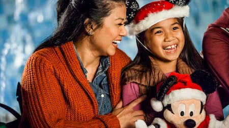 A mother smiles next to her daughter who is wearing a holiday Mickey ear hat and holding a Mickey Santa plush