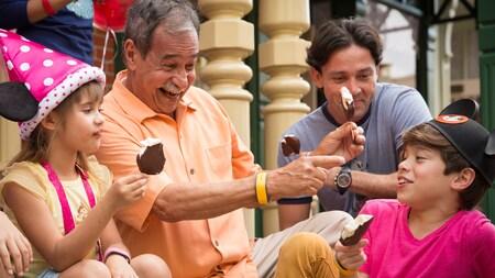 Un abuelo, el padre y 2 el nieto se ríen y juegan mientras comen barras heladas Mickey Mouse