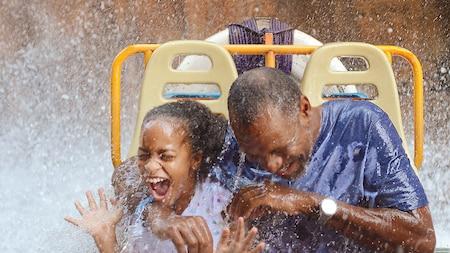 Una niña y su abuelito se doblan de la risa mientras se empapan en un paseo en un Parque Temático