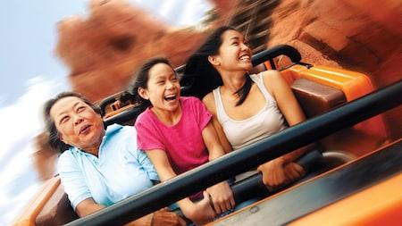 Una mamá y sus hijas sonríen emocionadas, mientras disfrutan de un paseo en el Big Thunder Mountain Railroad