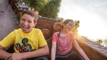 Un niño y una niña se ríen emocionados mientras descienden a toda velocidad una colina en la montaña rusa de un Parque Temático