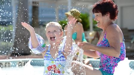 Una abuela y su nieta en una piscina se ríen mientras la pequeña salpica agua
