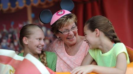 La abuela con orejas de Minnie Mouse ser ríe con sus 2nietas mientras están en una atracción en un Hotel.