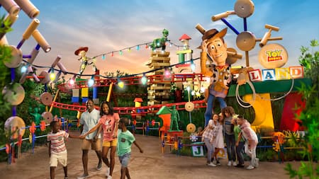 Two families with tween children stand near a statue of Woody and a sign that reads Toy Story Land