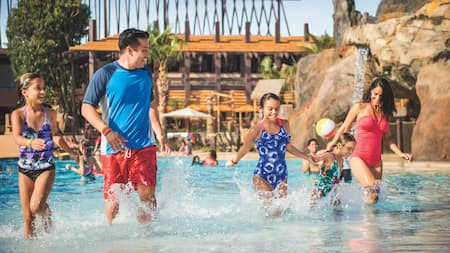 A family of 5 walks near the edge of a beach-style pool at a Disney Resort hotel