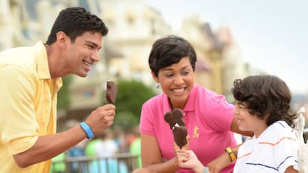 A mother, father and son laughing together while eating Mickey ice cream bars at Magic Kingdom park