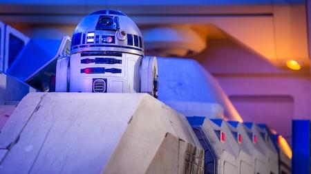 R2-D2 sale de su posición desde dentro de una nave en una habitación intensamente iluminada