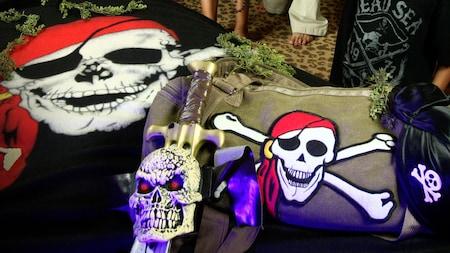 Una espada con una cabeza de esqueleto con apariencia enojada descansa sobre un bolso marinero adornado con parche con una calavera grande y dos huesos en forma de cruz