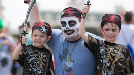 Un padre con maquillaje de esqueleto y un pañuelo y su hijo vestido como un pirata levanta espadas de juguete