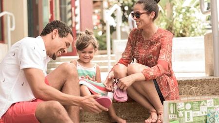 Um pai coloca um sapato da Sanuk nos pés de sua filha enquanto a mãe observa, segurando o outro par