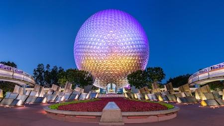 Des monorails passent des deux côtés de Spaceship Earth alors que la pièce maîtresse emblématique d'Epcot s'illumine la nuit