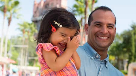A smiling man holds a smiling little girl