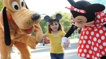 Pluto and Minnie Mouse hold hands with a little girl