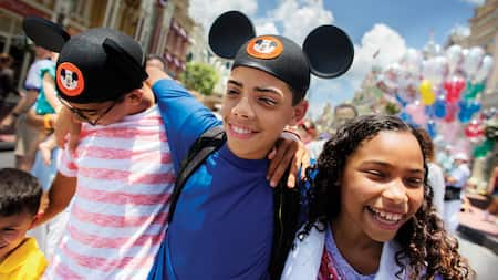 A group of kids wearing Mickey hats walk arm in arm
