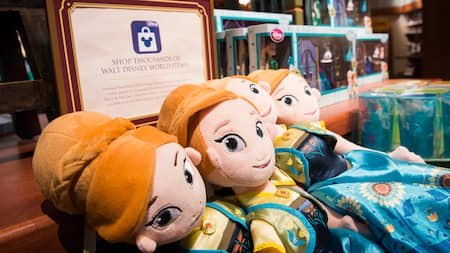 "Muñecas de peluche en una tienda con un letrero que dice ""Shop Thousands of Walt Disney World Items"""