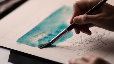 Hands hold a watercolor paintbrush while applying paint over a pencil drawing of a passenger boat